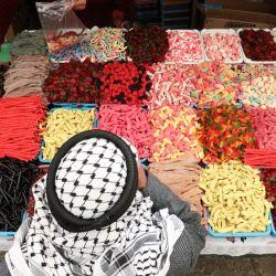 Un vendedor ambulante palestino vende caramelos y dulces en la Ciudad Vieja de Hebrón en la Cisjordania ocupada por Israel. | Foto:Hazem Bader / AFP