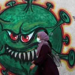 Una mujer palestina pasa junto a un mural de coronavirus. | Foto:Ashraf Amra / DPA
