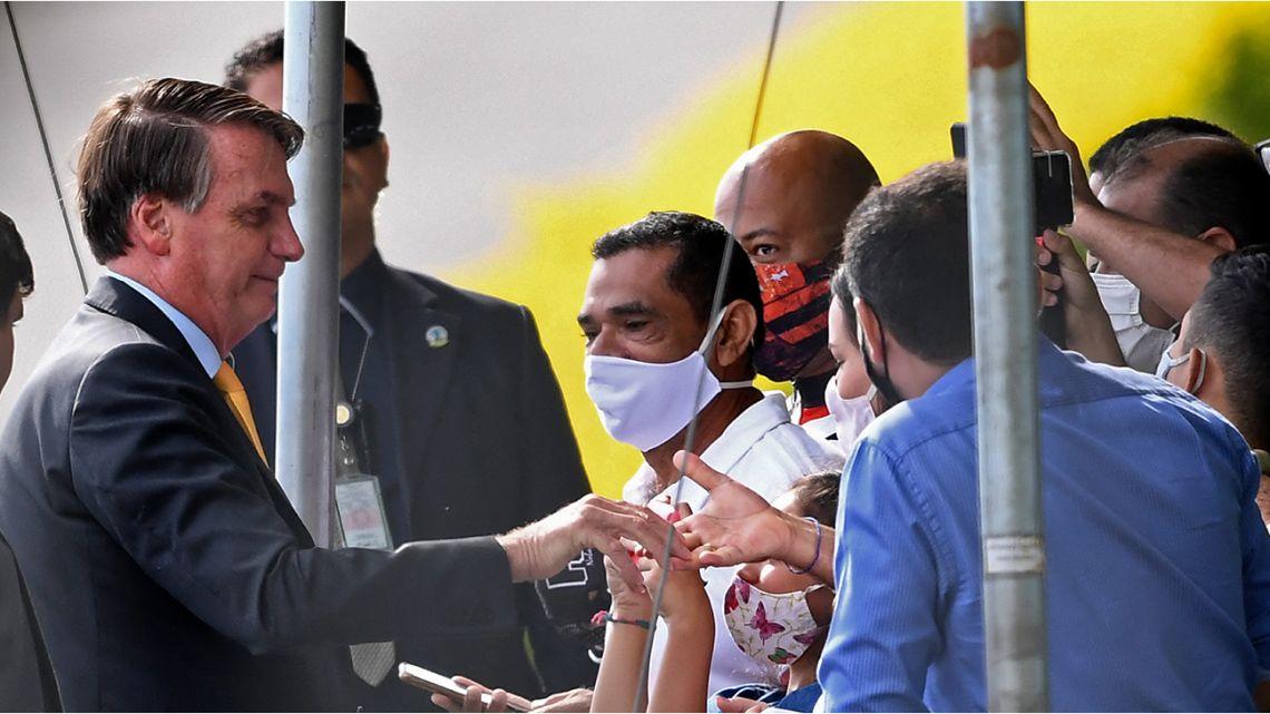 Brazilian President Jair Bolsonaro (L) greets supporters as he leaves the Alvorada Palace in Brasilia, on April 13, 2021.