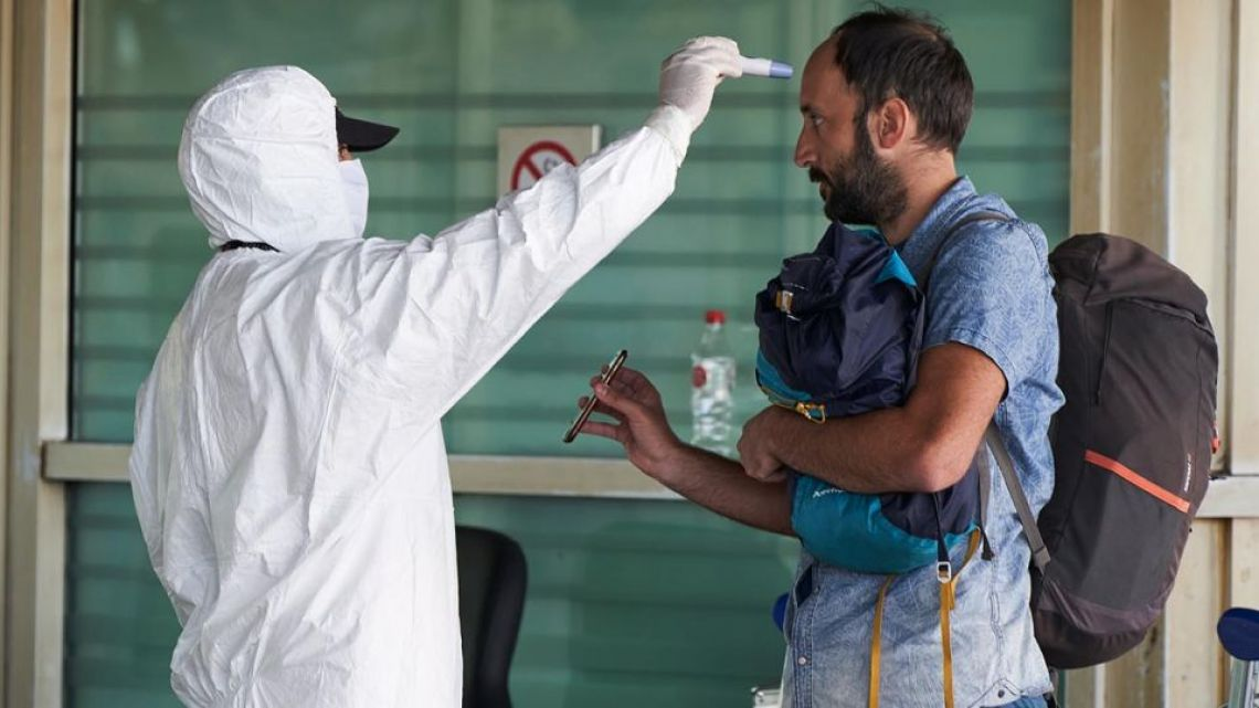 A citizen has his temperature checked in Buenos Aires.
