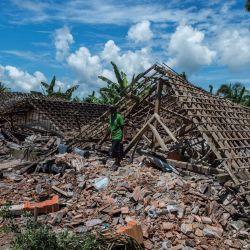 Un hombre recoge artículos de una estructura dañada en Malang, Java Oriental, un día después de que un terremoto de magnitud 6,0 sacudiera la costa de la principal isla de Java en Indonesia. | Foto:Juni Kriswanto / AFP