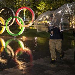 La gente pasa por los Anillos Olímpicos cerca del Estadio Nacional, sede principal de los Juegos Olímpicos y Paralímpicos de Tokio 2020, 100 días antes de la ceremonia de apertura en Tokio. | Foto:Charly Triballeau / AFP