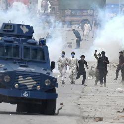 Partidarios del partido Tehreek-e-Labbaik Pakistan (TLP) arrojan piedras sobre el vehículo blindado de la policía durante una protesta contra el arresto de su líder cuando exigía la expulsión del embajador francés por las representaciones del profeta Mahoma, en el barrio de Barakahu en Islamabad. | Foto:Aamir Qureshi / AFP