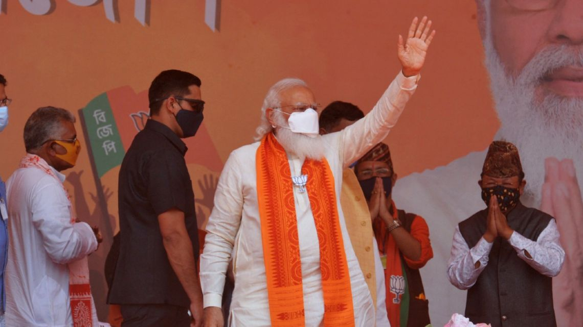 Indian Prime Minister Narendra Modi (centre) waves to supporters in a rally meeting during the ongoing Phase 4 of West Bengal's assembly election, at Kawakhali on the outskirts of Siliguri on April 10, 2021.