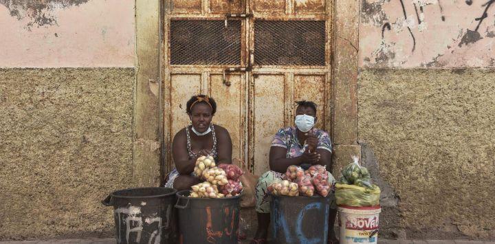 Vendedores de verduras se sientan en la calle en Praia, Cabo Verde.