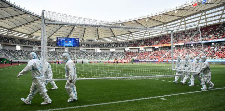 Los trabajadores que usan equipo de protección personal (EPP) llevan un arco antes del partido de fútbol femenino de la segunda etapa del play-off de clasificación para los Juegos Olímpicos de Tokio 2020 entre China y Corea del Sur en el Estadio del Centro Deportivo Olímpico de Suzhou en Suzhou, provincia de Jiangsu.