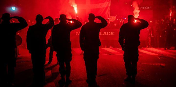 Los manifestantes saludan mientras participan en una marcha organizada por el movimiento anti-restricción