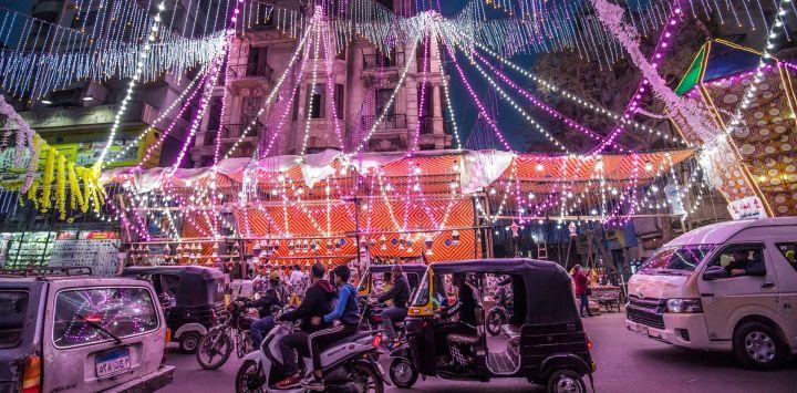 Vehículos, motocicletas y rickshaws motorizados pasan por un puesto que vende linternas de Ramadán a lo largo de una calle principal en el suburbio norte de Shubra (hogar de una gran población cristiana) de la capital de Egipto, El Cairo, en el comienzo del mes sagrado de ayuno musulmán del Ramadán.
