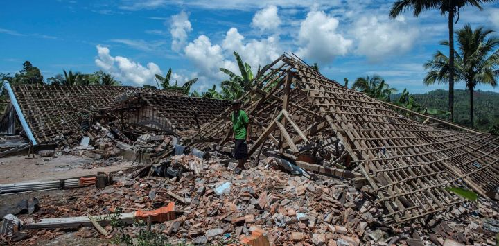 Un hombre recoge artículos de una estructura dañada en Malang, Java Oriental, un día después de que un terremoto de magnitud 6,0 sacudiera la costa de la principal isla de Java en Indonesia.