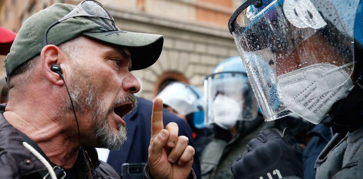 Un manifestante choca con agentes de policía tras la manifestación de los trabajadores de la lavandería y el turismo contra las restricciones del coronavirus.
