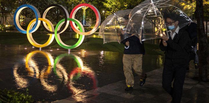 La gente pasa por los Anillos Olímpicos cerca del Estadio Nacional, sede principal de los Juegos Olímpicos y Paralímpicos de Tokio 2020, 100 días antes de la ceremonia de apertura en Tokio.