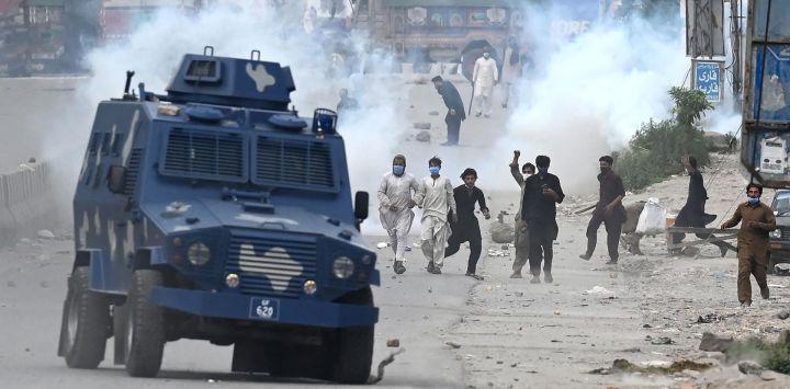 Partidarios del partido Tehreek-e-Labbaik Pakistan (TLP) arrojan piedras sobre el vehículo blindado de la policía durante una protesta contra el arresto de su líder cuando exigía la expulsión del embajador francés por las representaciones del profeta Mahoma, en el barrio de Barakahu en Islamabad.