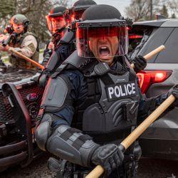 Los oficiales de policía se ponen a cubierto mientras chocan con los manifestantes después de que un oficial disparó y mató a un hombre negro en Brooklyn Center, Minneapolis, Minnesota.   Foto:Kerem Yucel / AFP
