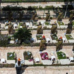 Esta imagen tomada en Yom HaZikaron (el Día Conmemorativo de Israel) muestra una vista aérea de mujeres soldados israelíes realizando saludos junto a tumbas en el cementerio militar Kiryat Shaul en la ciudad costera mediterránea de Tel Aviv.   Foto:Jack Guez / AFP