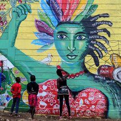 Artistas del proyecto de arte local, Art 360, pintan para completar el mural para crear conciencia sobre la salud mental y los cambios climáticos globales en el barrio pobre de Kibera en Nairobi, Kenia.   Foto:Gordwin Odhiambo / AFP