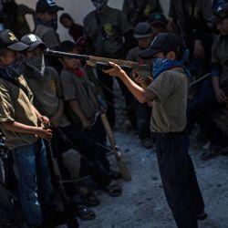 Los niños se reúnen mientras se preparan para participar en una demostración de capacitación de la fuerza de vigilancia de la Coordinadora Regional de Autoridades Comunitarias (CRAC-PF), en la vereda Ayahualtempa, Estado de Guerrero, México. - La autodefensa CRAC-PF El grupo capacita a niños de hasta cinco años para que puedan protegerse de los grupos delictivos relacionados con las drogas que operan en la zona.   Foto:Pedro Pardo / AFP
