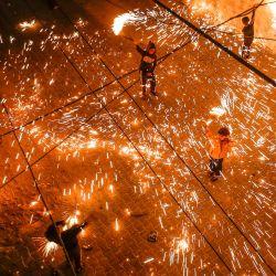 Jóvenes palestinos balancean bengalas de fuegos artificiales caseros, mientras la gente celebra la noche anterior al mes sagrado de ayuno musulmán del Ramadán, en el campamento de Rafah para refugiados palestinos en el sur de la Franja de Gaza.   Foto:Mahmud Hams / AFP