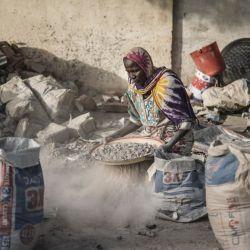 Habiba, una trituradora de grava que cree tener entre 50 y 60 años, tamiza con un tamiz improvisado para separar la grava de la arena cerca de la Cite International des Affaires en N'Djamena.   Foto:Marco Longari / AFP