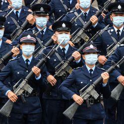 Los oficiales de policía realizan una nueva marcha a paso de ganso, el mismo estilo que usan la policía y las tropas en China continental, en la escuela de policía de la ciudad durante una jornada de puertas abiertas para conmemorar el Día de la Educación en Seguridad Nacional en Hong Kong. | Foto:Anthony Wallace / AFP