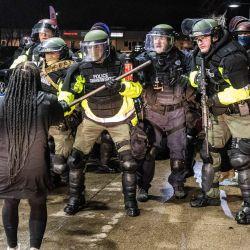 Estados Unidos, Brooklyn Center: un manifestante se para frente a los oficiales de policía durante los enfrentamientos en la gasolinera Pump N 'Munch cerca del Departamento de Policía de Brooklyn Center luego de una protesta contra el asesinato de Daunte Wright, un hombre negro de 20 años que murió baleado por la policía en una parada de tráfico en la ciudad estadounidense de Brooklyn Center. | Foto:DPA