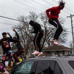 Los manifestantes se paran en la parte superior de un automóvil de la policía mientras se enfrentan después de que un oficial disparó y mató a un hombre negro en Brooklyn Center, Minneapolis, Minnesota. | Foto:Kerem Yucel / AFP