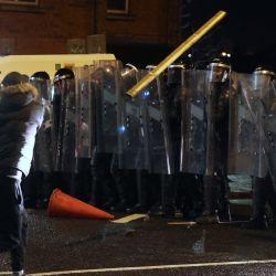 Un hombre lanza un objeto hacia la policía antidisturbios. La violencia volvió a estallar en las calles de Belfast, y la policía utilizó cañones de agua contra los manifestantes. | Foto:Liam Mcburney / PA Wire / DPA