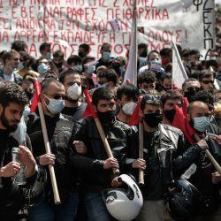 Los estudiantes sostienen pancartas y banderas durante una manifestación en las calles de Atenas, exigiendo la apertura de universidades, cerradas desde hace un año debido a la pandemia Covid-19, y protestando contra la creación de una fuerza policial especial con el objetivo de lucha contra la violencia en las universidades griegas. | Foto:Louisa Gouliamaki / AFP