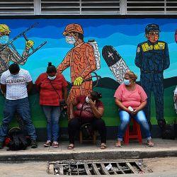 La gente espera información sobre sus familiares infectados por Covid-19, en las inmediaciones del Hospital Escuela Universitario, en Tegucigalpa.   Foto:Orlando Sierra / AFP