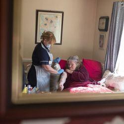 Julie Fletcher, líder del equipo de vacunación en casa, administra una dosis de la vacuna AstraZeneca / Oxford Covid-19 a la paciente Gillian Marriott en su casa en Hasland, cerca de Chesterfield, en el centro de Inglaterra. | Foto:Oli Scarff / AFP