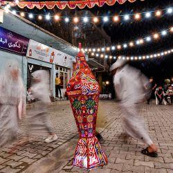 Esta imagen de larga exposición tomada en la primera noche del mes sagrado de ayuno musulmán del Ramadán en el casco antiguo de la ciudad de Mosul, en el norte de Irak, muestra a niños bailando alrededor de una linterna durante una celebración callejera organizada por una ONG cultural local. | Foto:Zaid Al-Obeidi / AFP