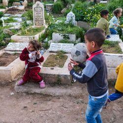 Los niños juegan junto a las tumbas en el cementerio de Ghoraba, que lleva el nombre del vecindario donde se encuentra en la ciudad portuaria de Trípoli, en el norte de Líbano, donde residen varias familias marginadas. | Foto:Ibrahim Chalhoub / AFP