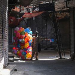 Un vendedor de globos pasa por un mercado cerrado en Lahore, cuando se impuso un bloqueo para controlar la propagación del coronavirus Covid-19. | Foto:Arif Ali / AFP