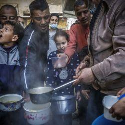 El palestino Walid al-Hattab distribuye sopa a las personas necesitadas durante el mes de ayuno musulmán del Ramadán en la ciudad de Gaza, en medio de la pandemia de COVID-19. | Foto:Mohammed Abed / AFP