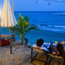 Esta foto muestra a una pareja mirando una lista de menú en un resort de playa a lo largo de la costa en el distrito de Klaeng, provincia de Rayong. | Foto:Romeo Gacag / AFP