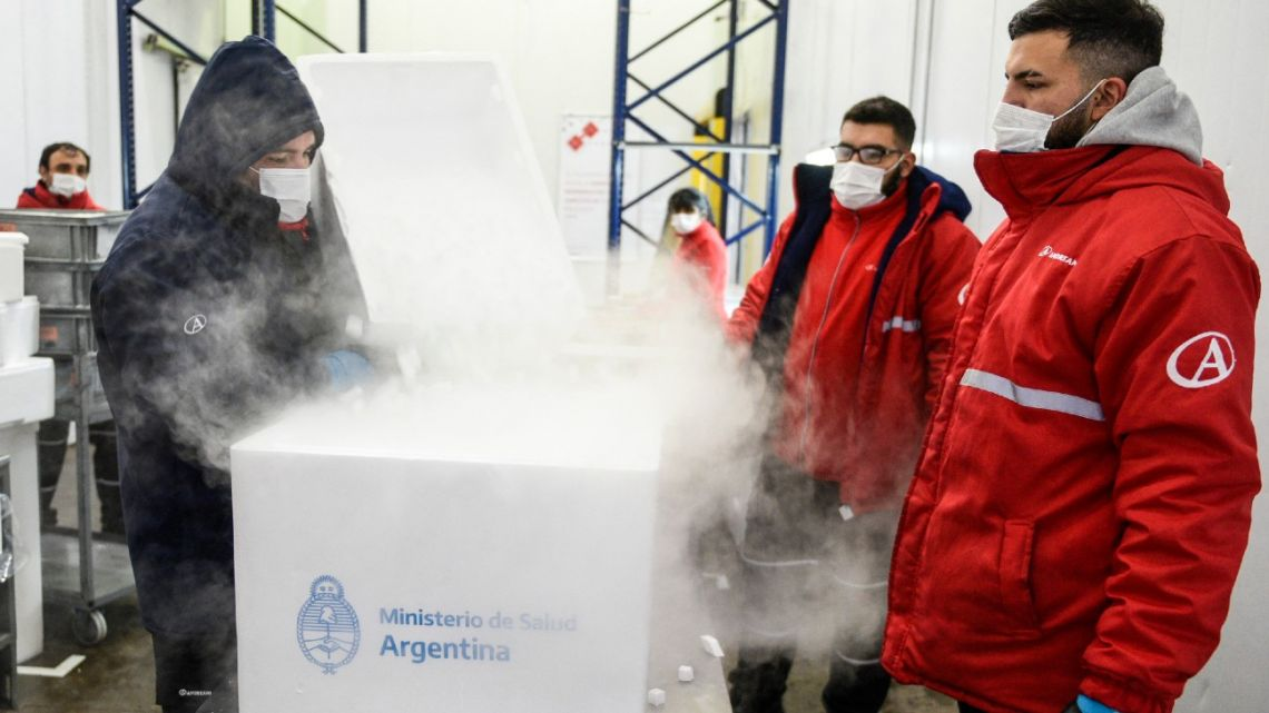 Handout picture released by the Presidency showing employees handling a shipment of 864,000 doses of the AstraZeneca vaccine from the Netherlands, as part of the Covax programme, at Ministro Pistarini International Airport in Ezeiza, Buenos Aires Province, on April 18, 2021.