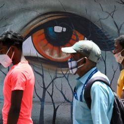Los peatones pasan junto a un mural en Mumbai. | Foto:Punit Paranjpe / AFP