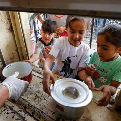 Los cocineros iraquíes sirven comida Iftar a los necesitados desde una cocina en la mezquita musulmana sunita Abdel Kader al-Kilani en el centro de Bagdad, durante el mes sagrado del Ramadán. | Foto:Ahmad Al-Rubaye / AFP