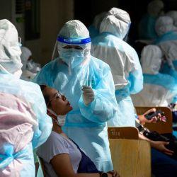 Un trabajador médico que usa EPP (equipo de protección personal) toma una muestra de hisopo de una mujer durante un evento de prueba masiva en un complejo deportivo en Bangkok, después del reciente brote de casos de coronavirus Covid-19 en Tailandia. | Foto:Mladen Antonov / AFP