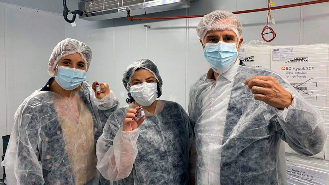 Health Minister Carla Vizzotti (centre), Presidential Advisor Cecilia Nicolini (left), and the President of Laboratorios Richmond, Marcelo Figueiras, pose for a photograph with a vial of locally made Sputnik V vaccine.