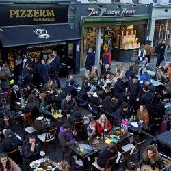 La gente se sienta en mesas al aire libre para comer y beber en bares y restaurantes reabiertos, en la calle en el área del Soho de Londres, siguiendo el paso dos de la hoja de ruta del gobierno para salir del tercer cierre nacional de Inglaterra.   Foto:Niklas Halle'n / AFP