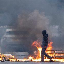Un leal camina frente a los escombros en llamas que bloquean la carretera en Lanark Way en el oeste de Belfast cuando se reanudaron los disturbios dentro de las comunidades leales de Irlanda del Norte después de una pausa para el funeral del príncipe Felipe, duque de Edimburgo.   Foto:Paul Faith / AFP