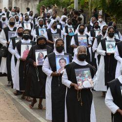 Los sacerdotes y monjas católicos llevan fotos mientras rinden homenaje a las víctimas asesinadas en los atentados del domingo de Pascua de 2019, en la iglesia de San Sebastián en Negombo.   Foto:Lakruwan Wanniarachchi / AFP