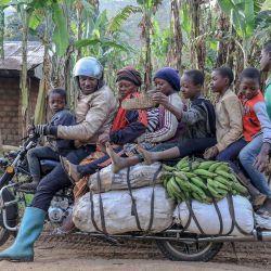 Emmanuel Wembe les dice a los pasajeros de su motocicleta que pongan los pies en las bolsas para evitar que se les atasquen las piernas, antes de partir con ellos en Bafoussam, Camerún. - Las motocicletas están personalizadas para tener varios metros de largo para ayudar al transporte de pasajeros y mercancías. | Foto:Daniel Beloumou Olomo / AFP