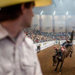 Ty Bertrand mira a un jinete a caballo en el San Angelo Stock Show and Rodeo, en San Angelo, Texas. - La primera noche del rodeo vio a una multitud agotada, el primer evento de rodeo que se llevó a cabo sin restricciones en San Angelo desde el comienzo de la pandemia. | Foto:Sergio Flores / AFP