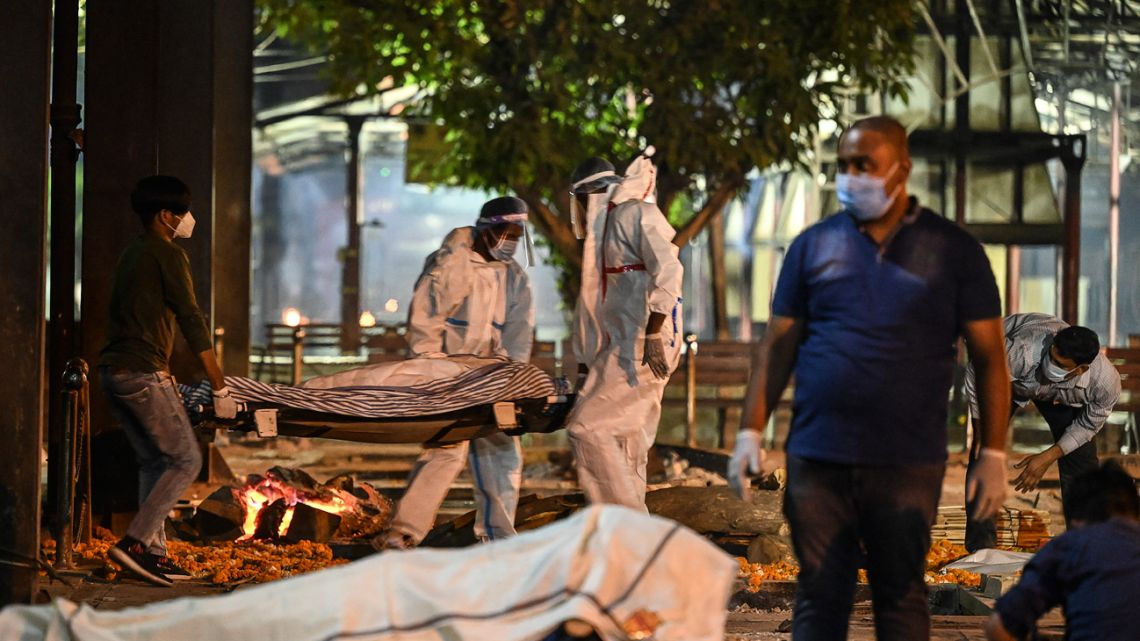Relatives and staff carry a dead body of a Covid-19 victim at Nigambodh Ghat Crematorium, on the banks of the Yamuna river in New Delhi in the early hour of April 22, 2021.