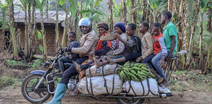 Emmanuel Wembe les dice a los pasajeros de su motocicleta que pongan los pies en las bolsas para evitar que se les atasquen las piernas, antes de partir con ellos en Bafoussam, Camerún. - Las motocicletas están personalizadas para tener varios metros de largo para ayudar al transporte de pasajeros y mercancías.