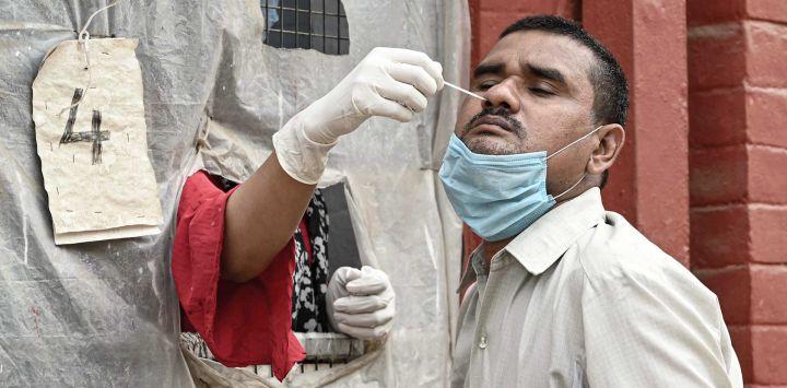India, Prayagraj: un trabajador de la salud toma una muestra de un hisopo de un hombre para la prueba de PCR del coronavirus (Covid-19).