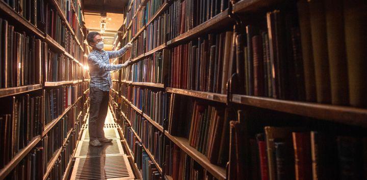 Chung Hoon, organiza los libros en las estanterías traseras de la Biblioteca de Londres en St James Square, mientras el gobierno alivia las restricciones actuales contra el coronavirus.