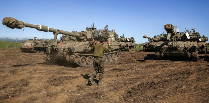 Un soldado israelí hace un gesto a los conductores de los cañones de artillería móvil obús M109 en una posición cerca de Moshav Sha'al en los Altos del Golán anexados por Israel.