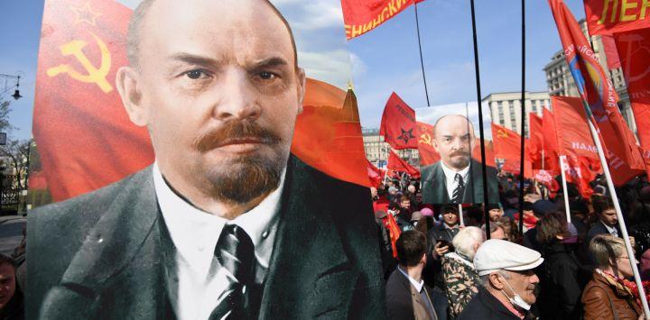 Los miembros y simpatizantes del partido comunista ruso llevan retratos de Vladimir Lenin mientras caminan hacia el mausoleo del fundador del estado soviético y líder revolucionario Vladimir Ilyich Ulyanov, también conocido como Lenin, para asistir a una ceremonia de colocación de flores que marca el 151 aniversario de su nacimiento, en la Plaza Roja de Moscú.